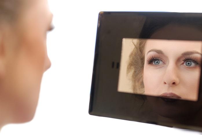 メイクした顔を鏡で確認する女性