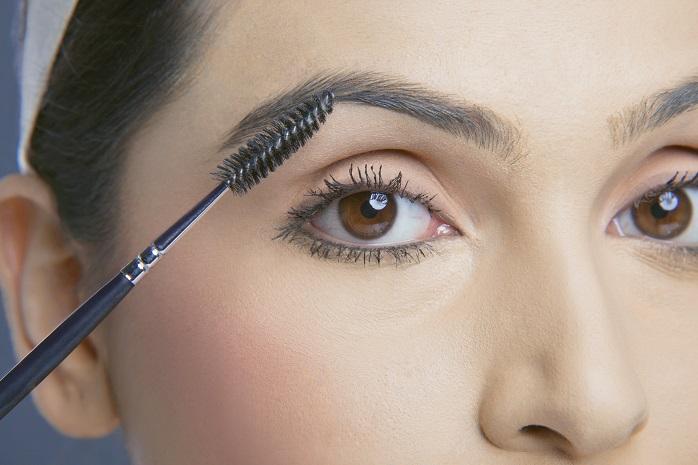 ブラシで眉毛の流れを整える女性